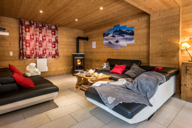 Lounge with sofas an logfire in chalet Snow Dream